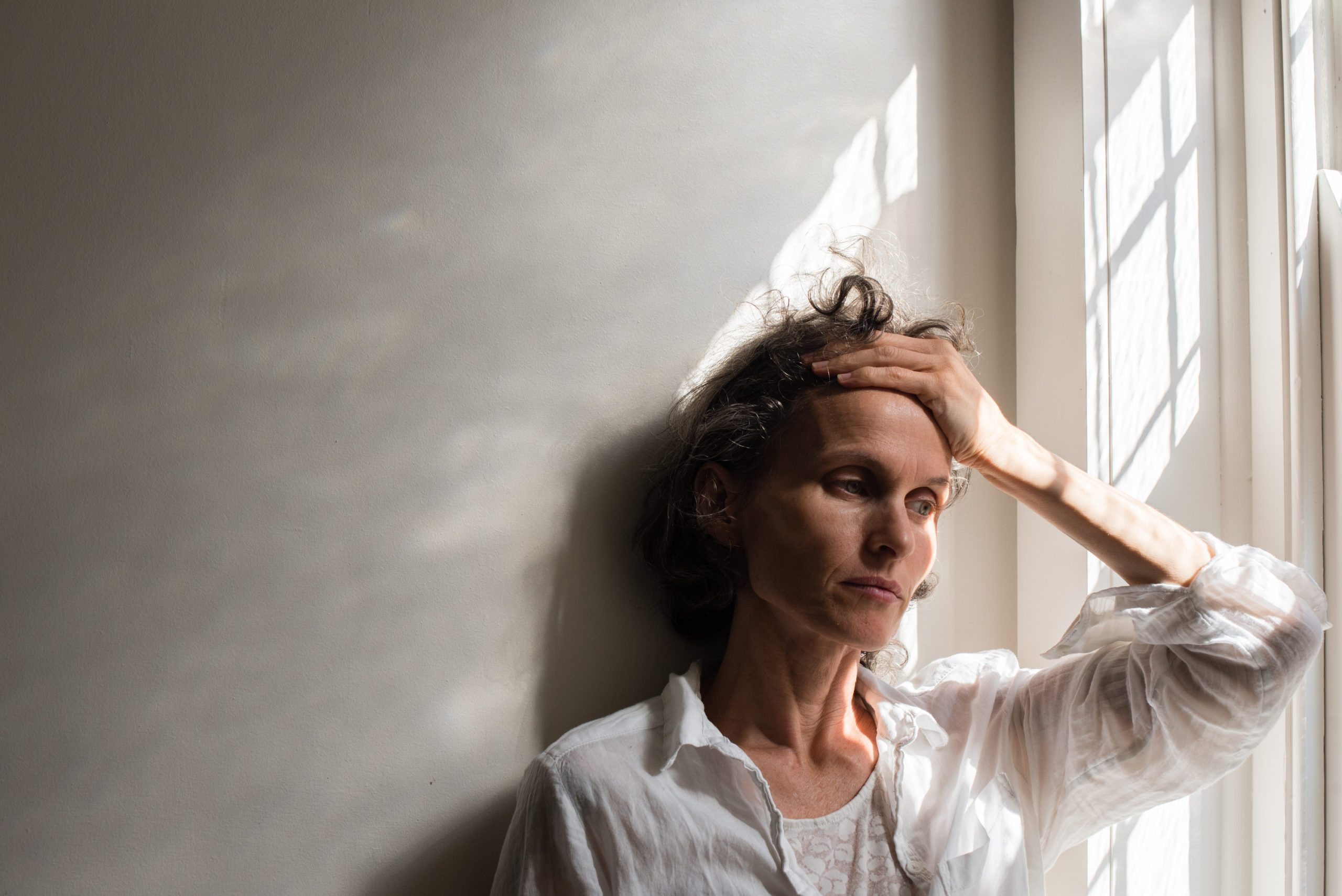 stressed woman at home with hand on forehead