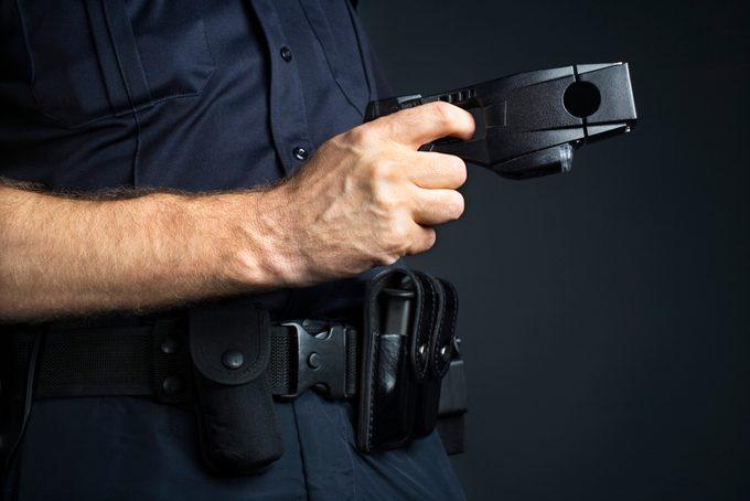 cropped shot of police officer holding taser stun gun