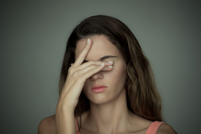 young woman with headache covering eyes