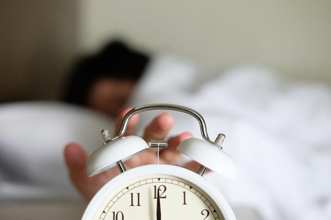 close up of hand on alarm clock