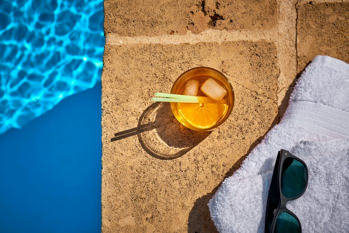 cocktail by the pool with towel and sunglasses overhead