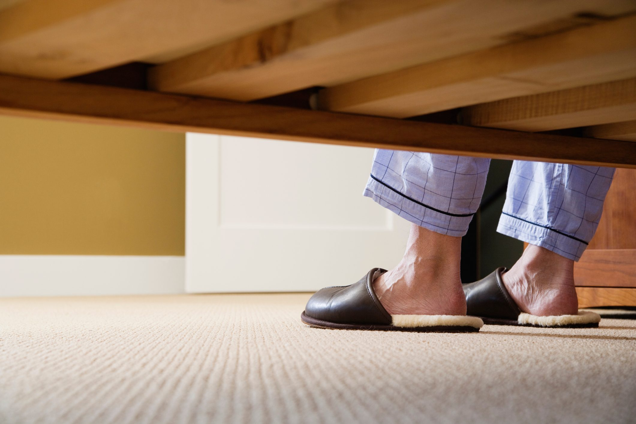 man's feet in slippers shot from under the bed