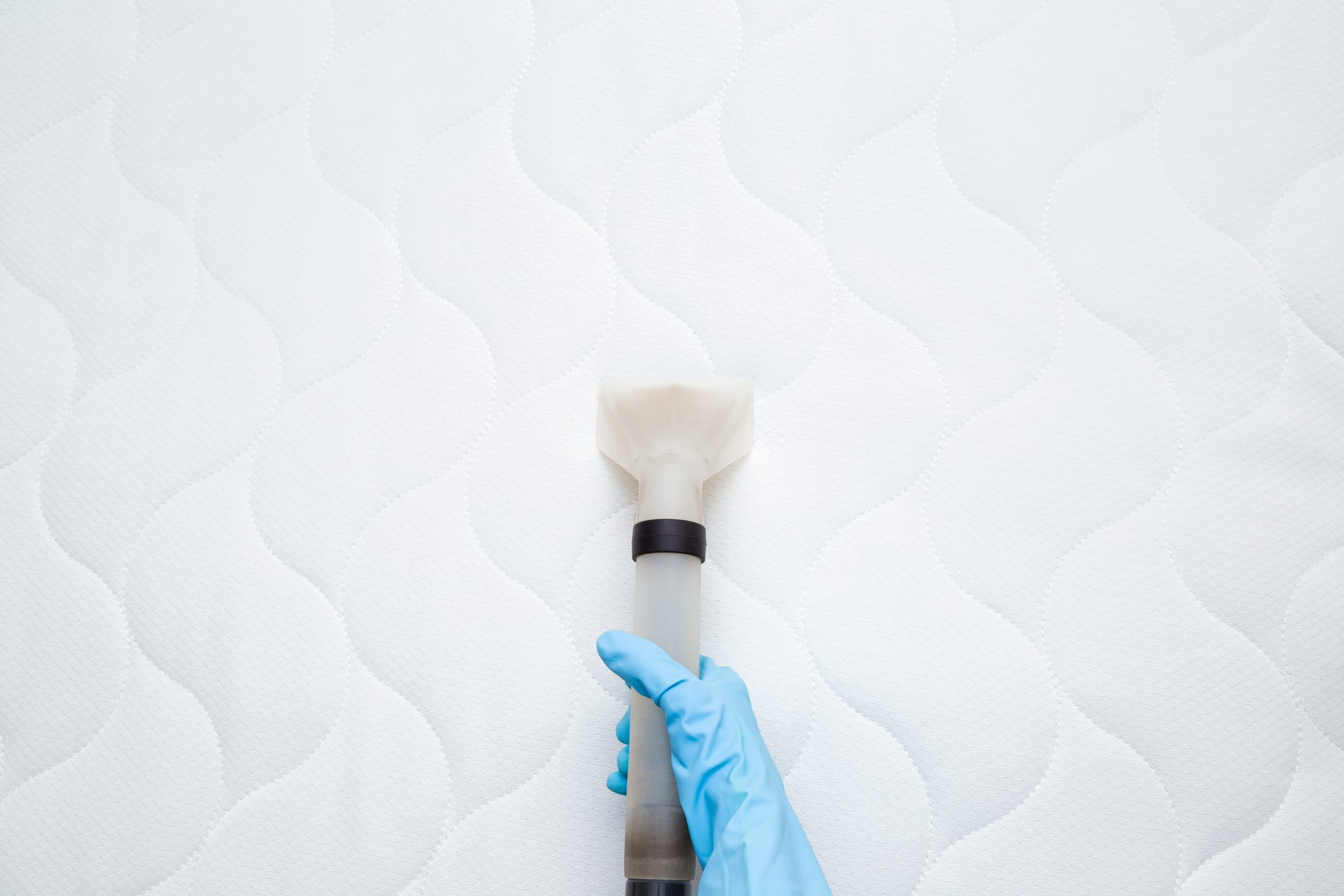 overhead shot of person vacuuming mattress