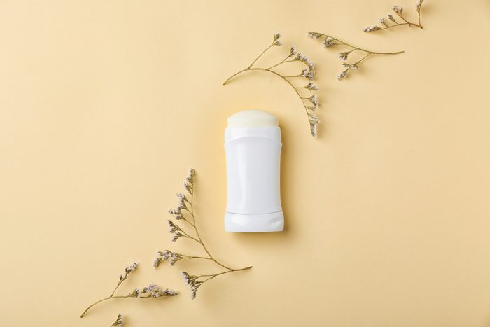 white deodorant stick on yellow background with flowers