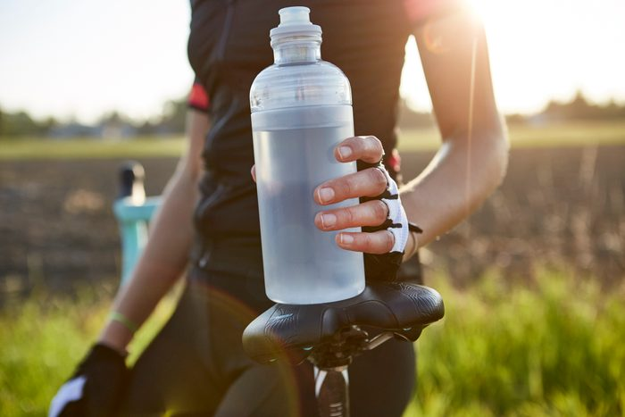 close up of cyclist holding water bottle