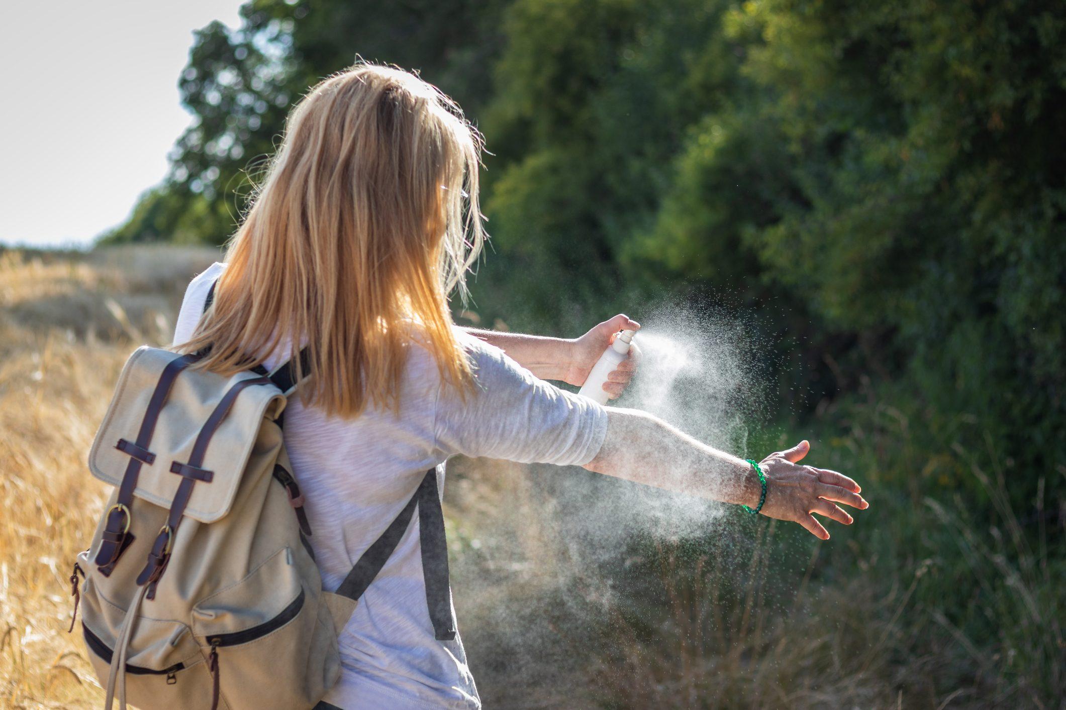 woman applying bug spray to arm