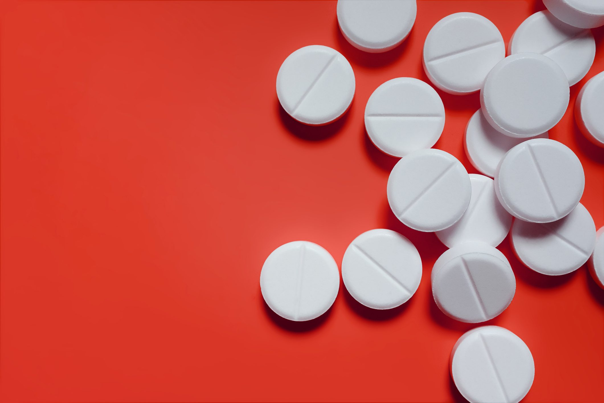 white pills on red background