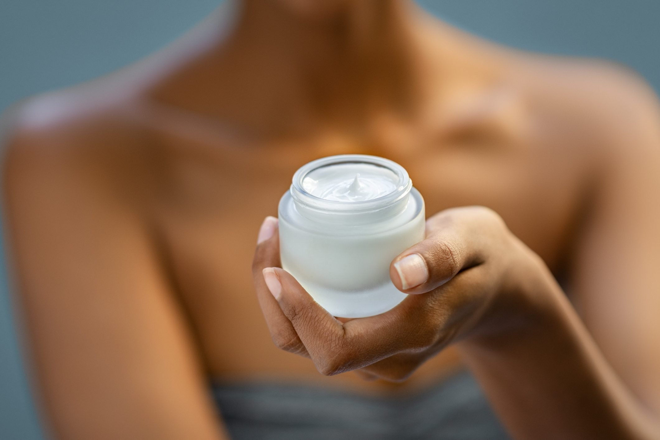 close up of woman holding moisturizer lotion in jar
