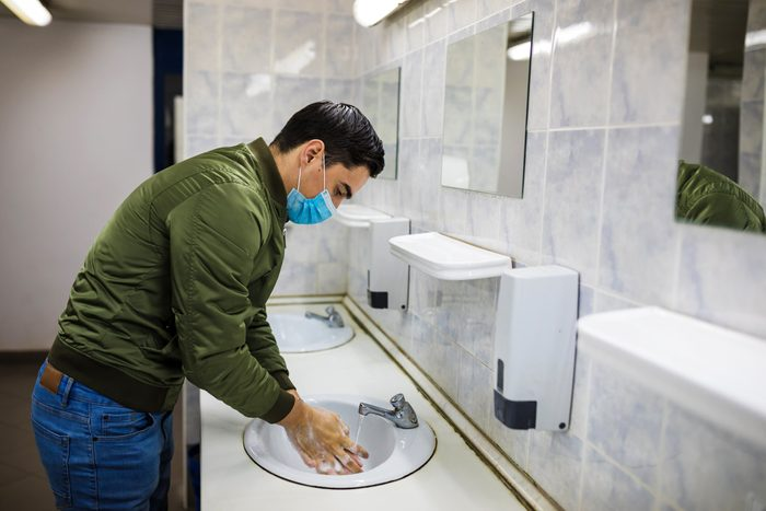 Man with face mask washing his hands in public bathroom