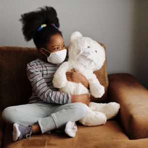 young girl with face mask and teddy bear at home during covid-19 pandemic