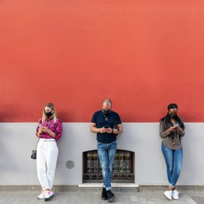 people wearing face masks leaning against red wall