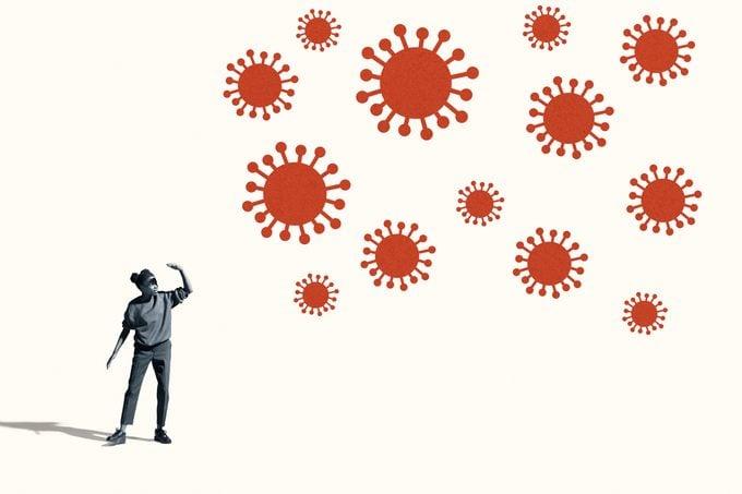woman shielding eyes from large coronavirus cells