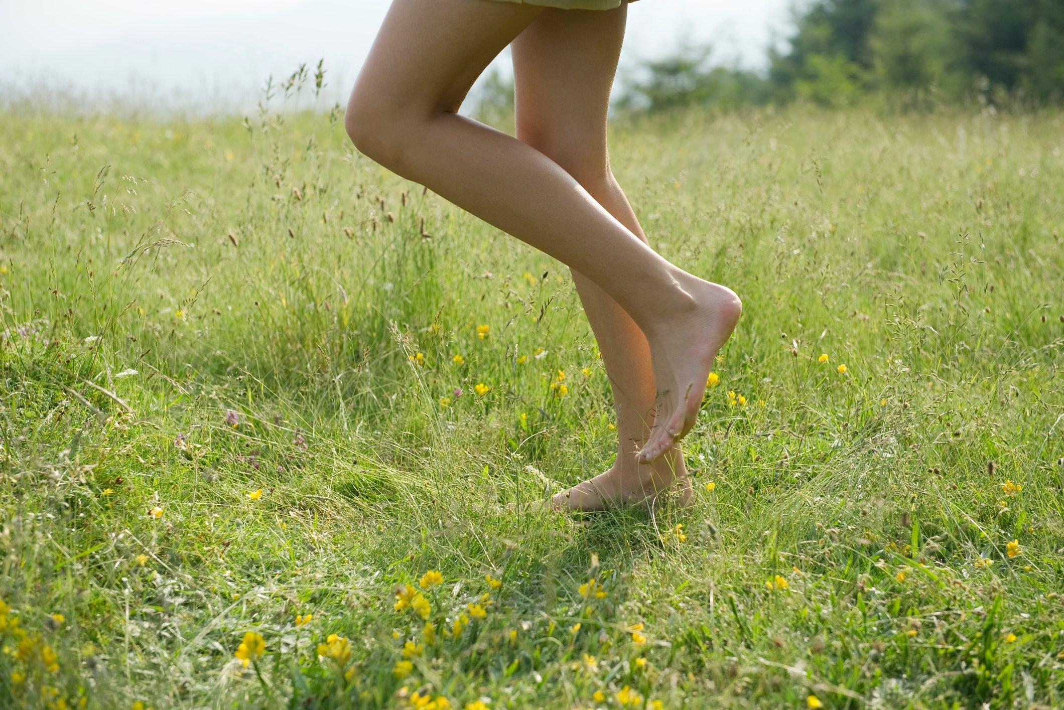 woman walking barefoot in grass field