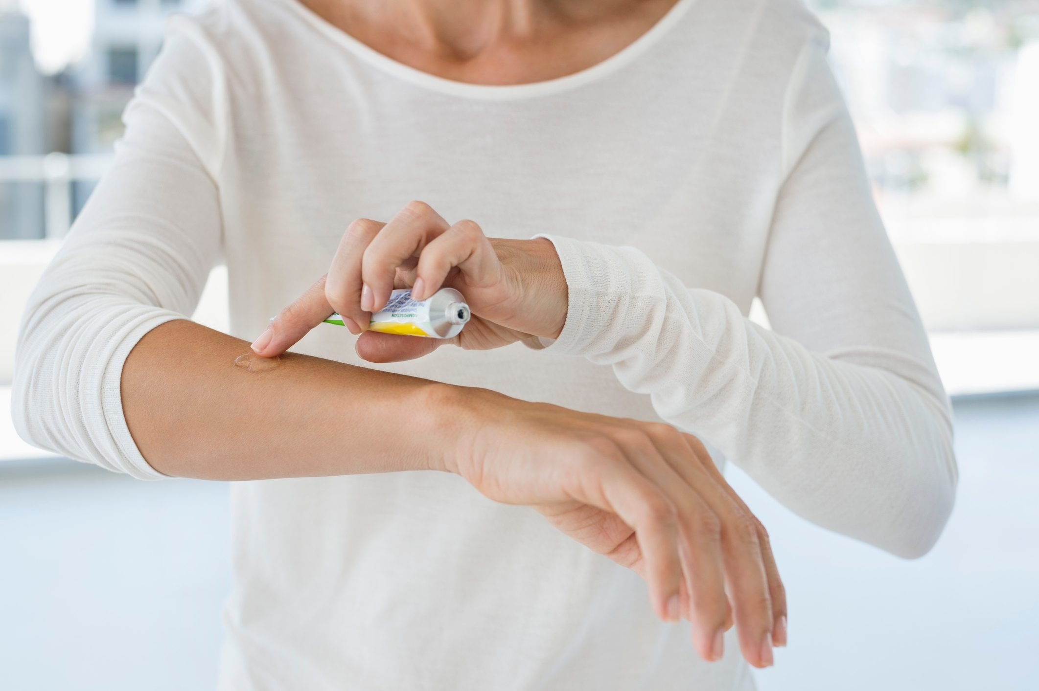 woman applying ointment on arm