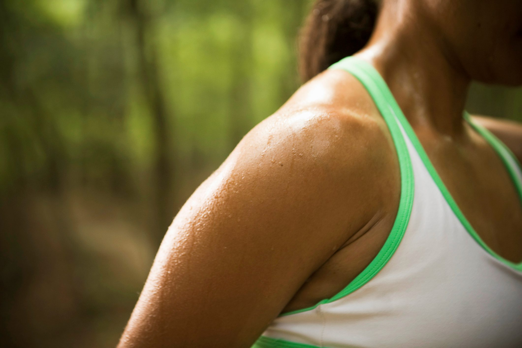 close up of woman's sweaty shoulder outside during exercise