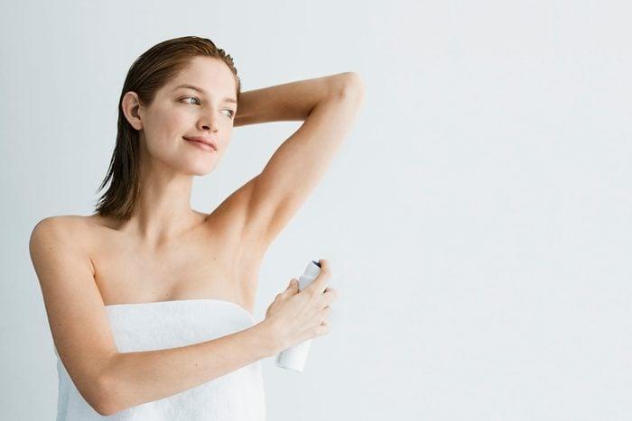 woman applying deodorant in bath towel