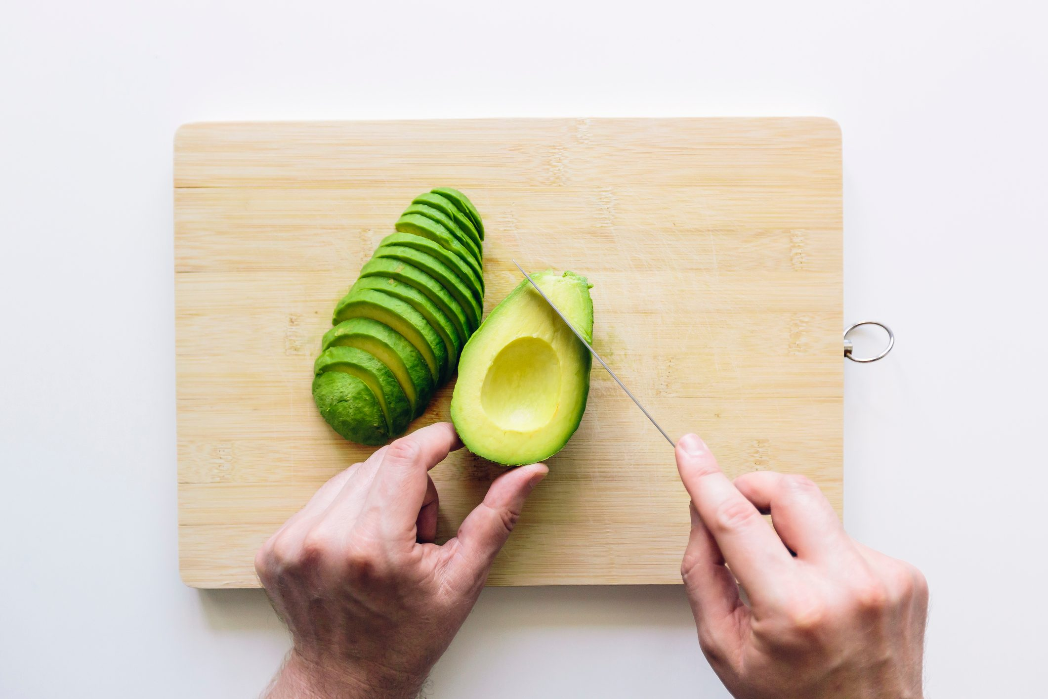 overhead shot of man slicing avocado