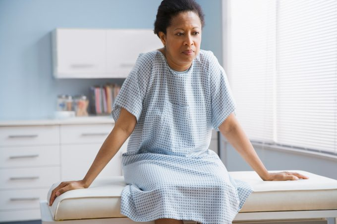 female patient sitting on examination table in doctor's office