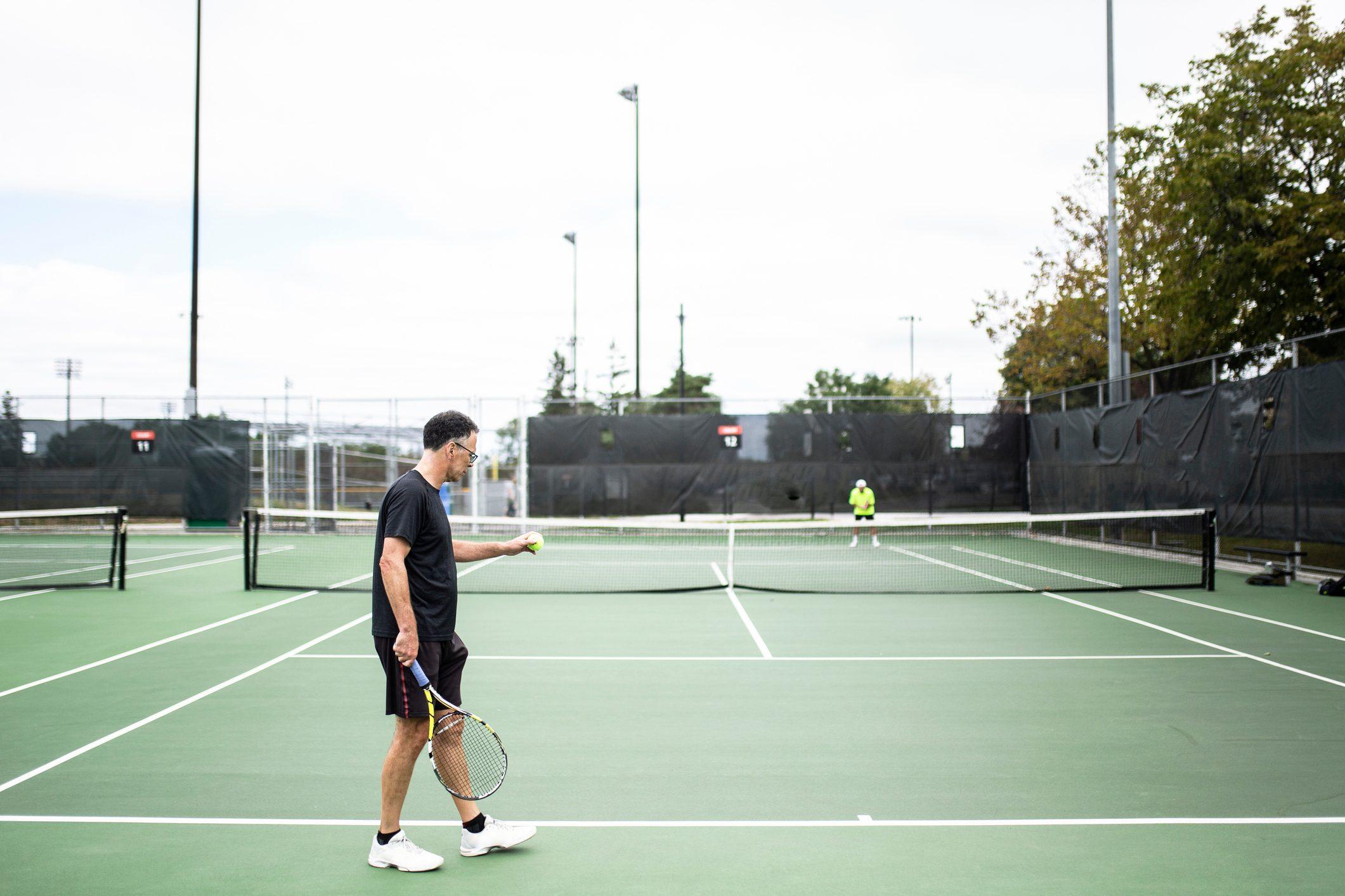 man playing tennis outside