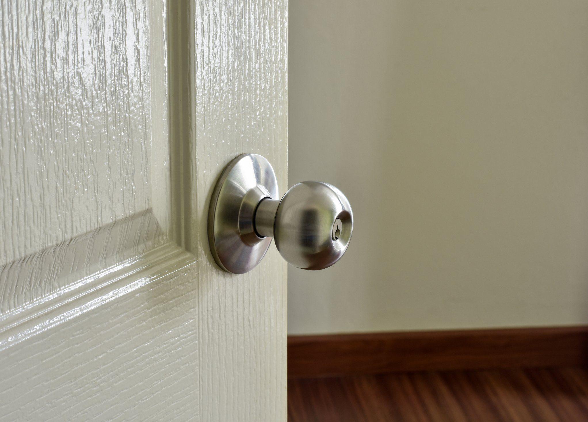 Metallic modern door knob on white wooden door.