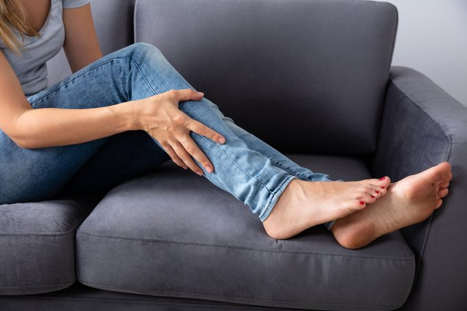 woman sitting on couch holding her leg in pain