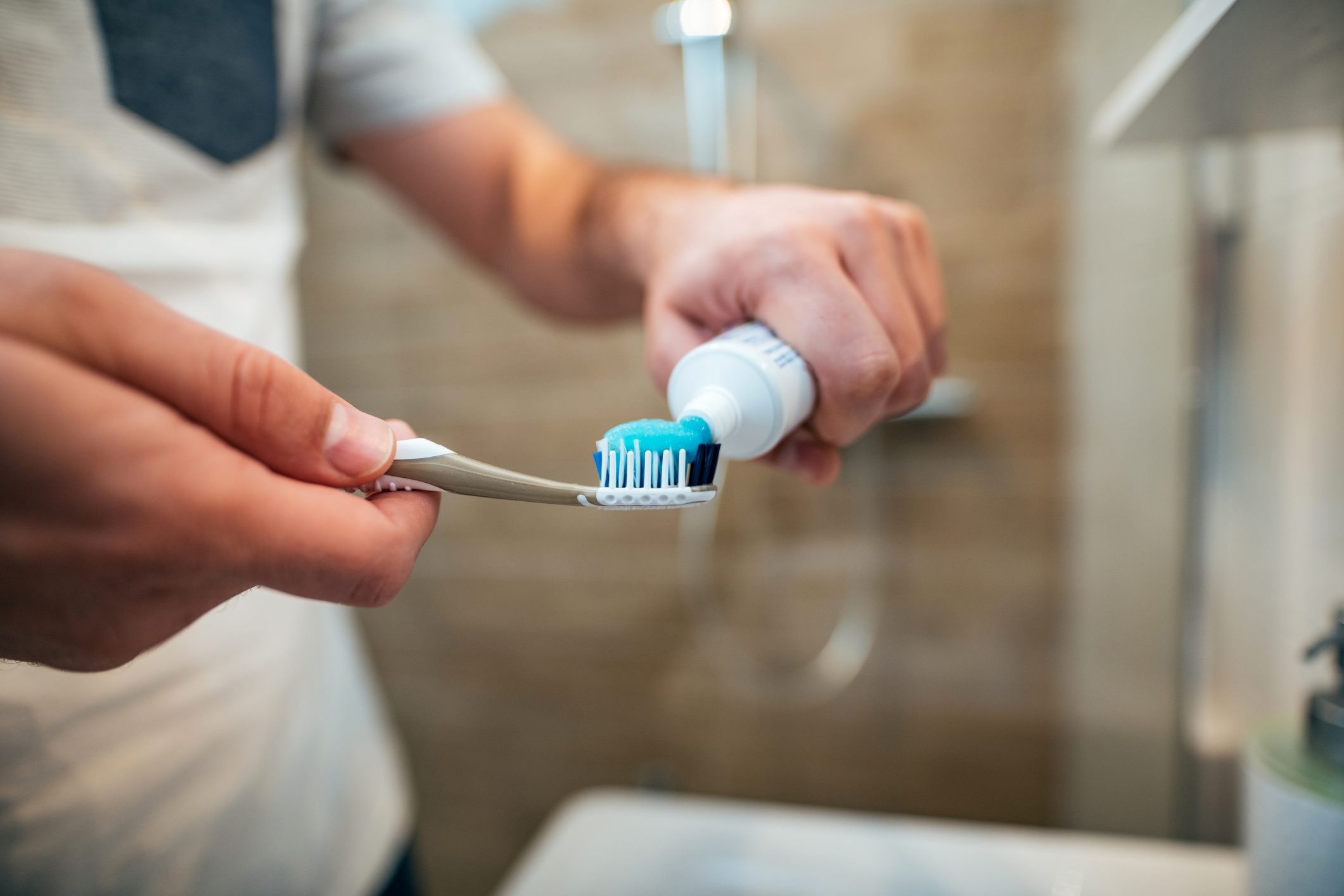 Dental health care concept. Close-up of man squeezes toothpaste on the toothbrush.