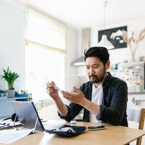 man checking blood sugar while working from home office