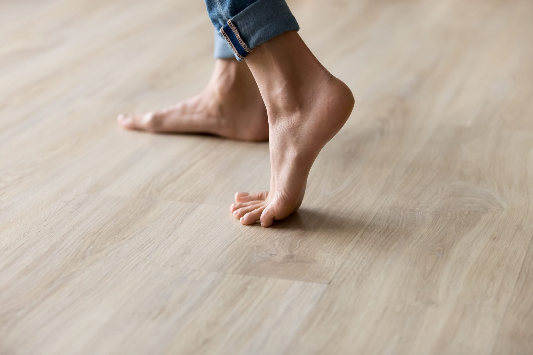 Side closeup view woman feet stands on warm wooden floor