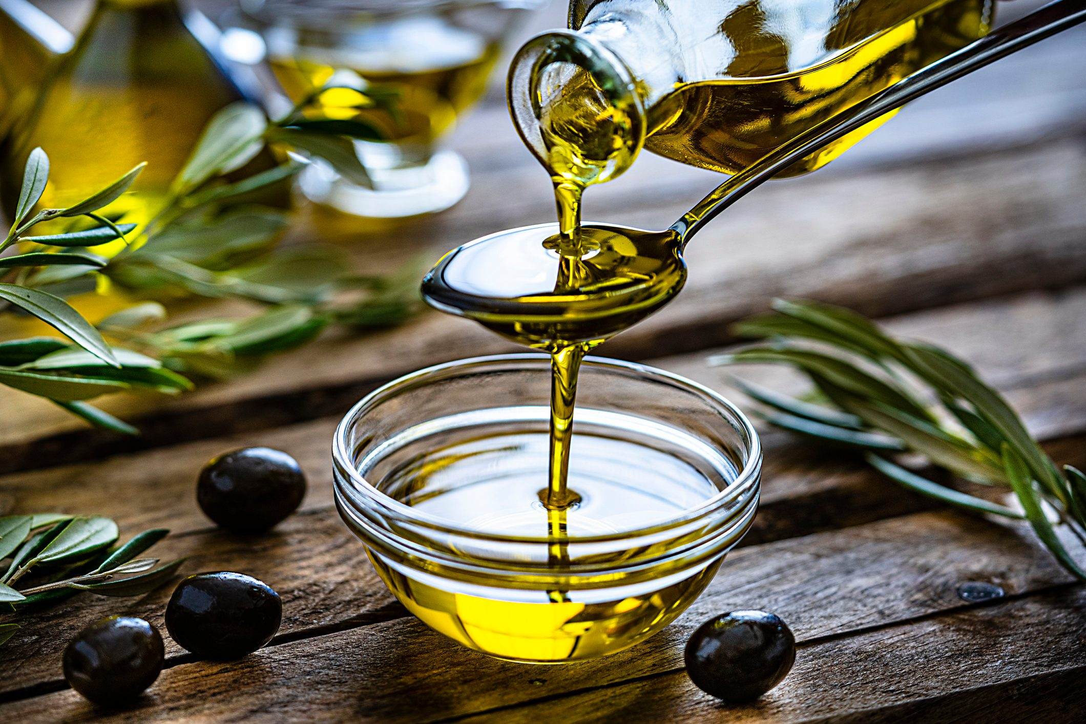 Pouring extra virgin olive oil in a glass bowl