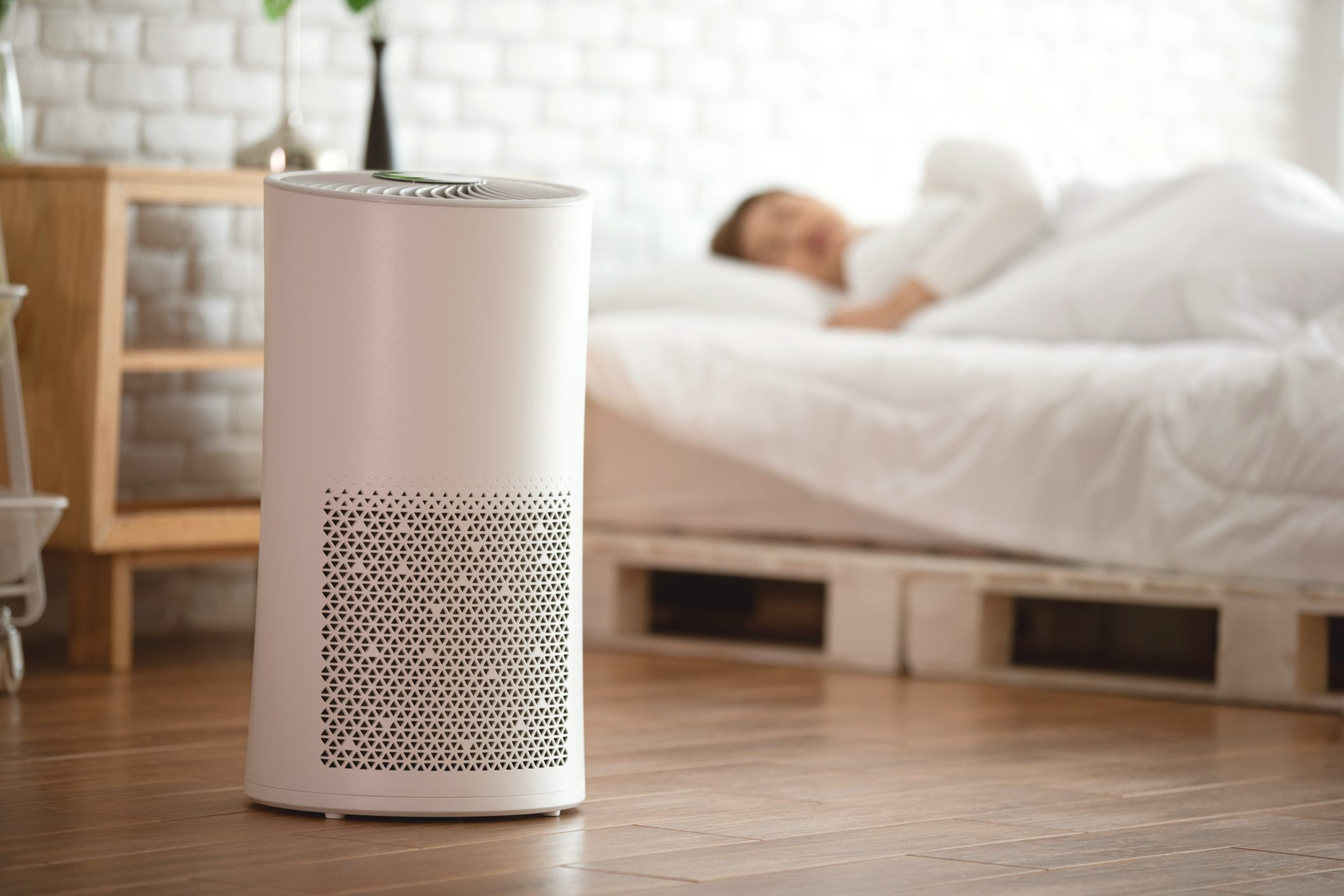 woman sleeping next to air purifier in bedroom