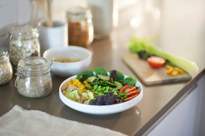Healthy vegan salad bowl and plastic free items on kitchen worktop.