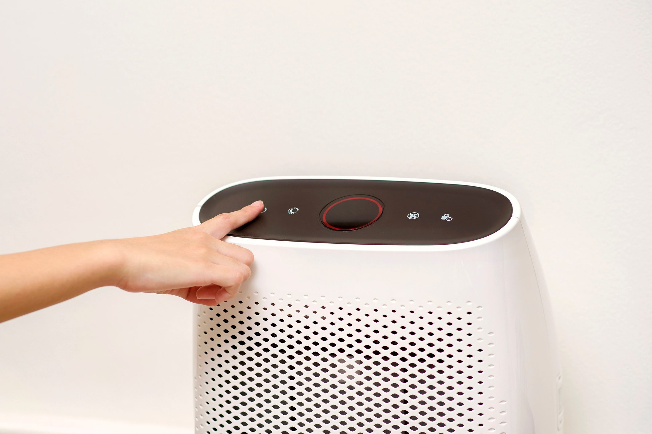 hand turning on air purifier in home