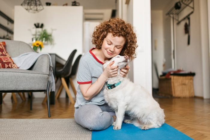 happy young woman hugging her dog at home