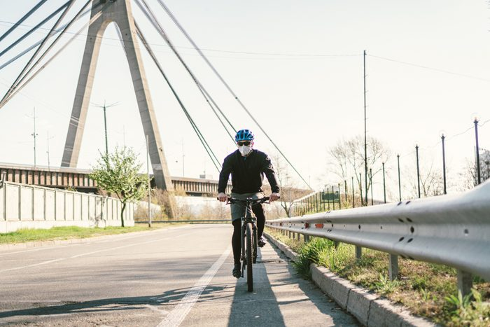 man riding a bike and wearing a face mask