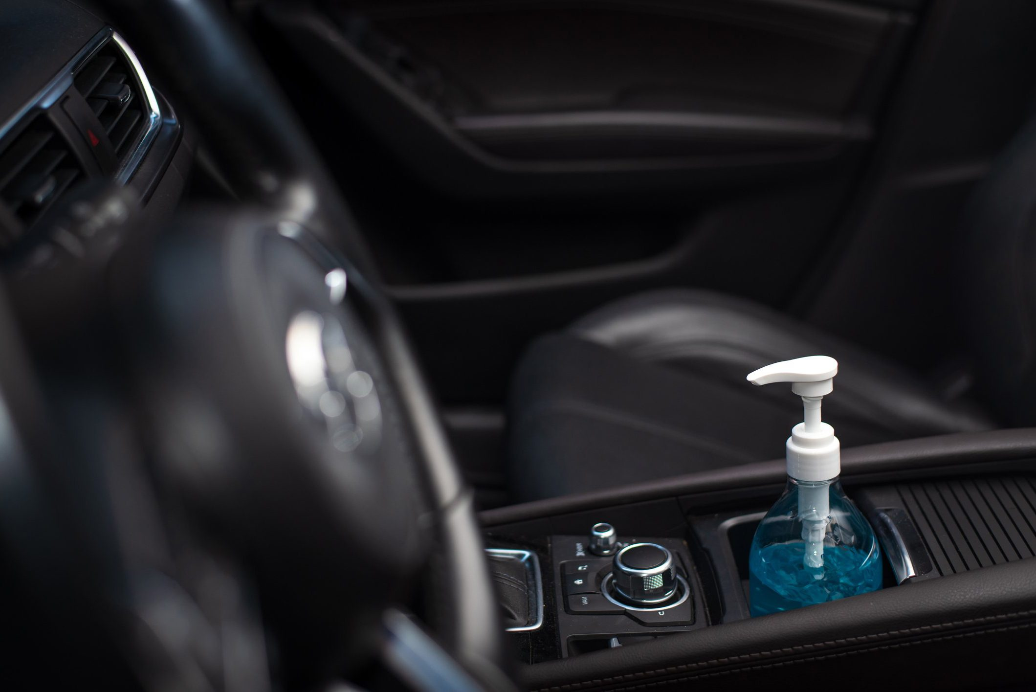 Bottle of blue sanitizer ethyl alcohol hand gel cleanser put in the car, prepare for protecting coronavirus, COVID-19