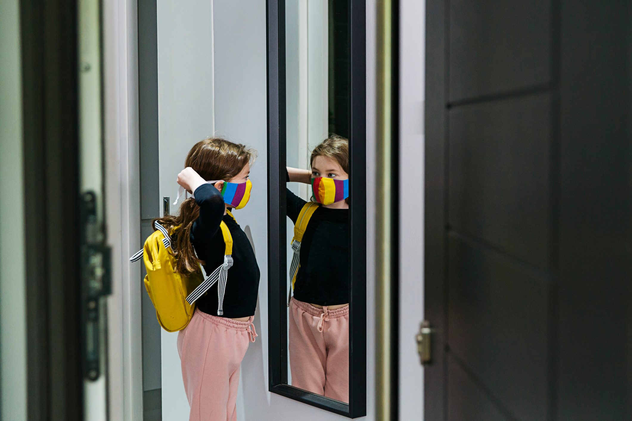 Young girl putting on her face mask in mirror by front door