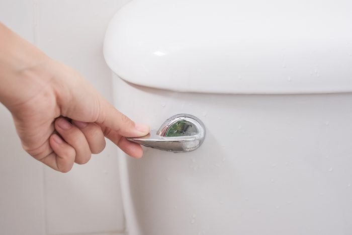Cropped Hand Of Person Flushing Toilet In Bathroom