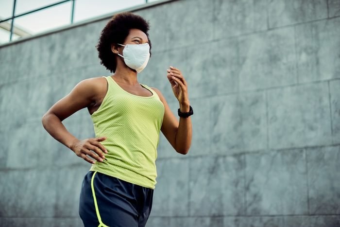 young woman running outside with face mask on