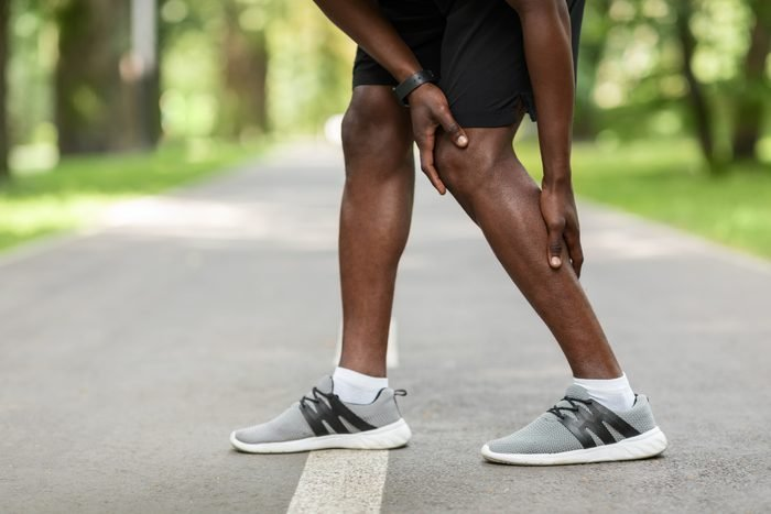 close up of man with pain in leg while exercising outside