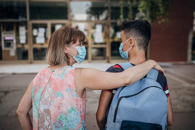 mother walking son to school wearing face masks