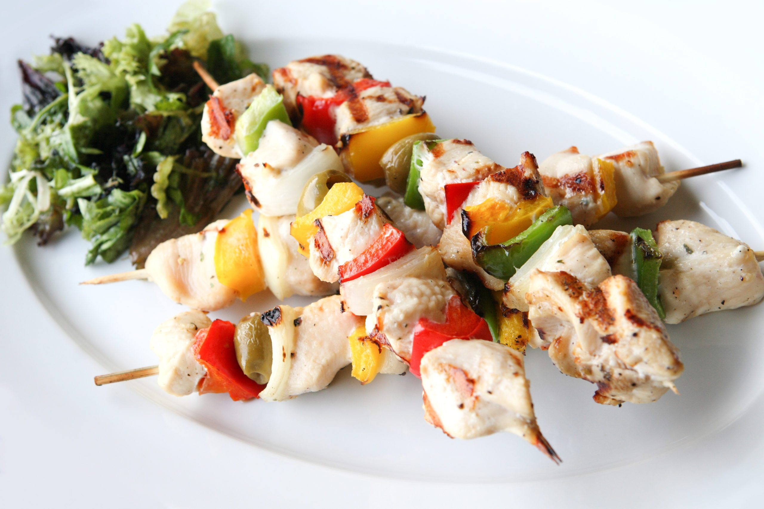 grilled chicken kabobs on plate with salad