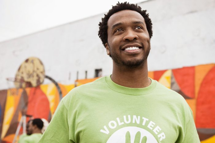 close up of smiling man wearing volunteer shirt