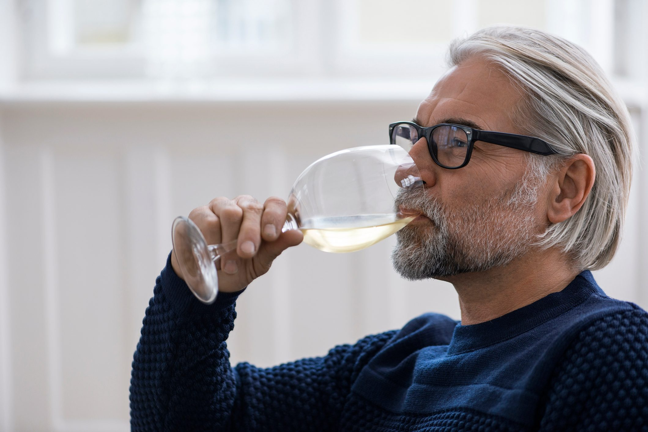 Mature man with glasses drinking white wine