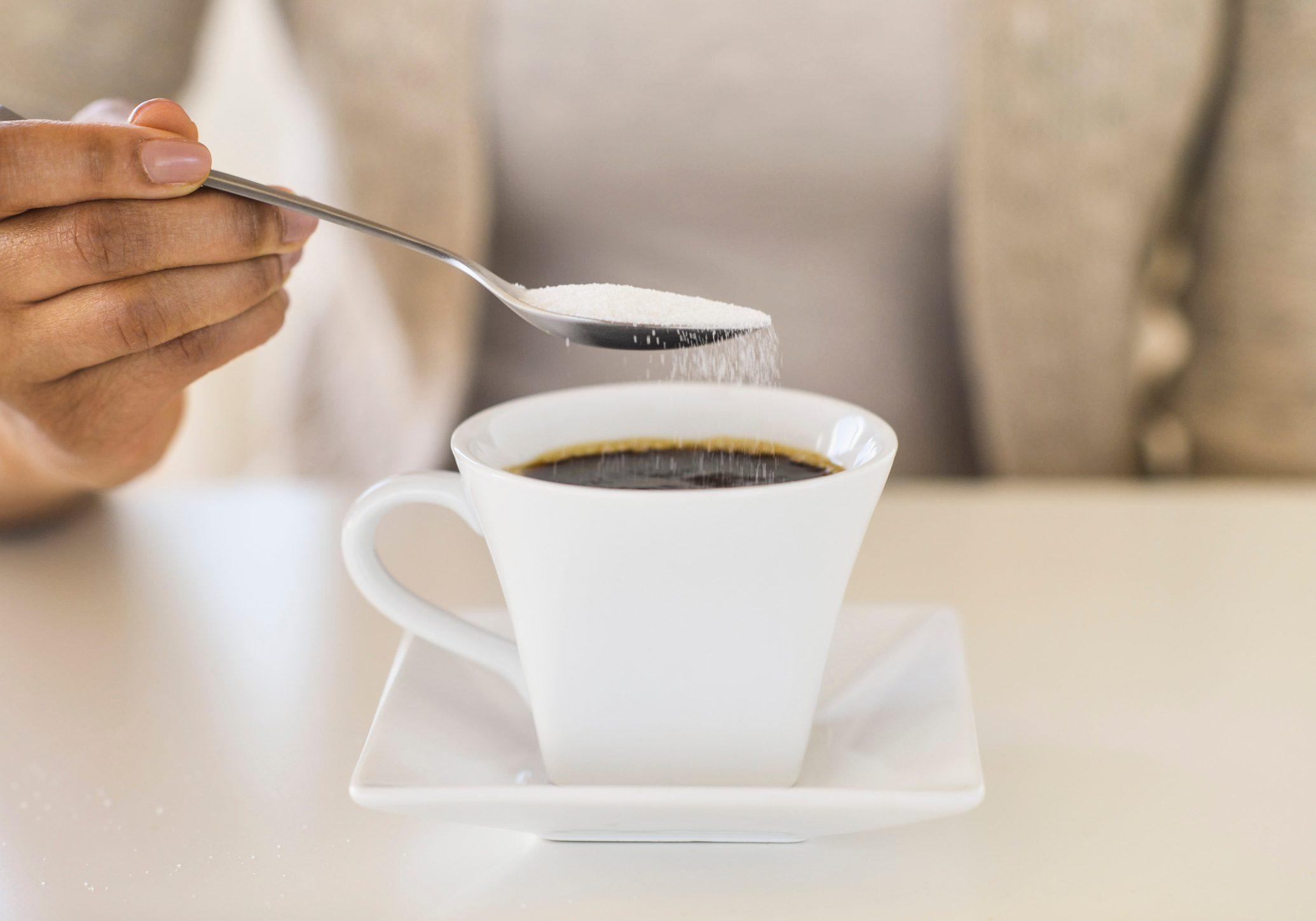 USA, New Jersey, Jersey City, Close-up of woman sweetening coffee