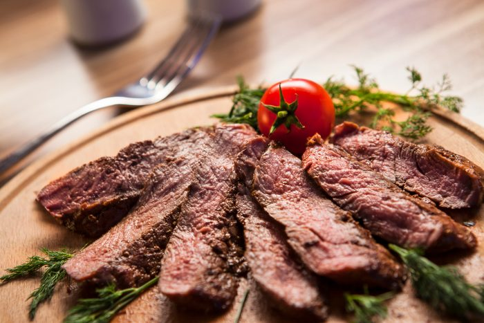 grilled steak on wood plate