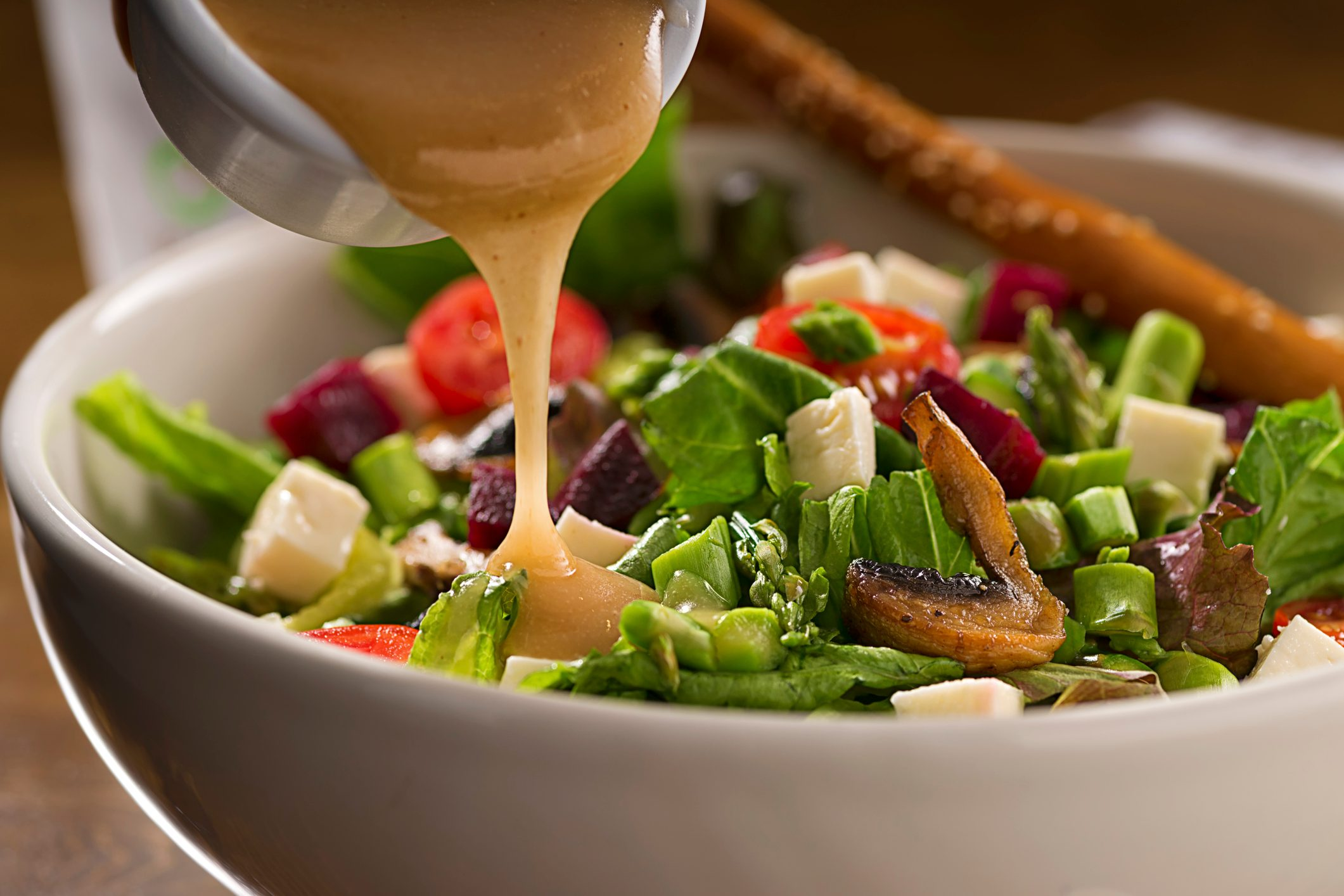 close up of dressing being poured onto salad