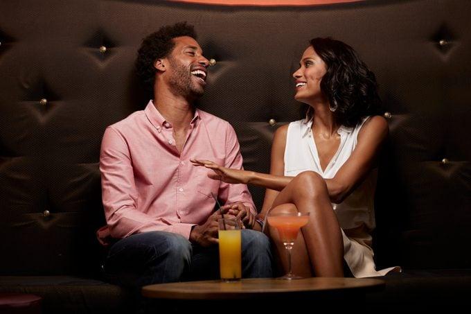 Cheerful couple conversing on sofa at nightclub