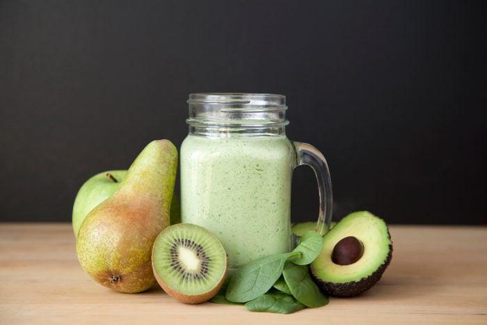 Still life of fresh kiwi, pear and avocado smoothie
