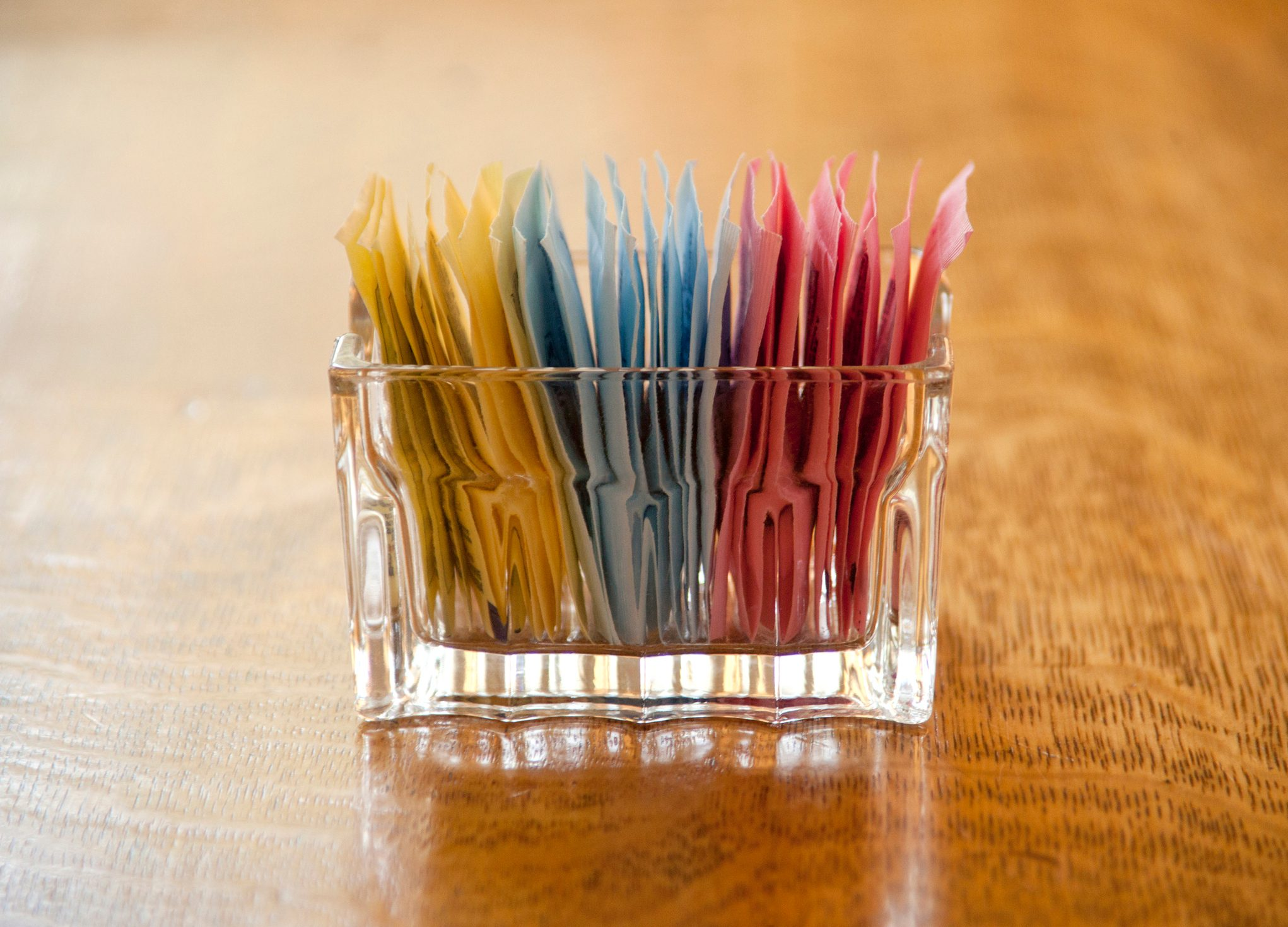 close up of artificial sweetener packs on table in restaurant