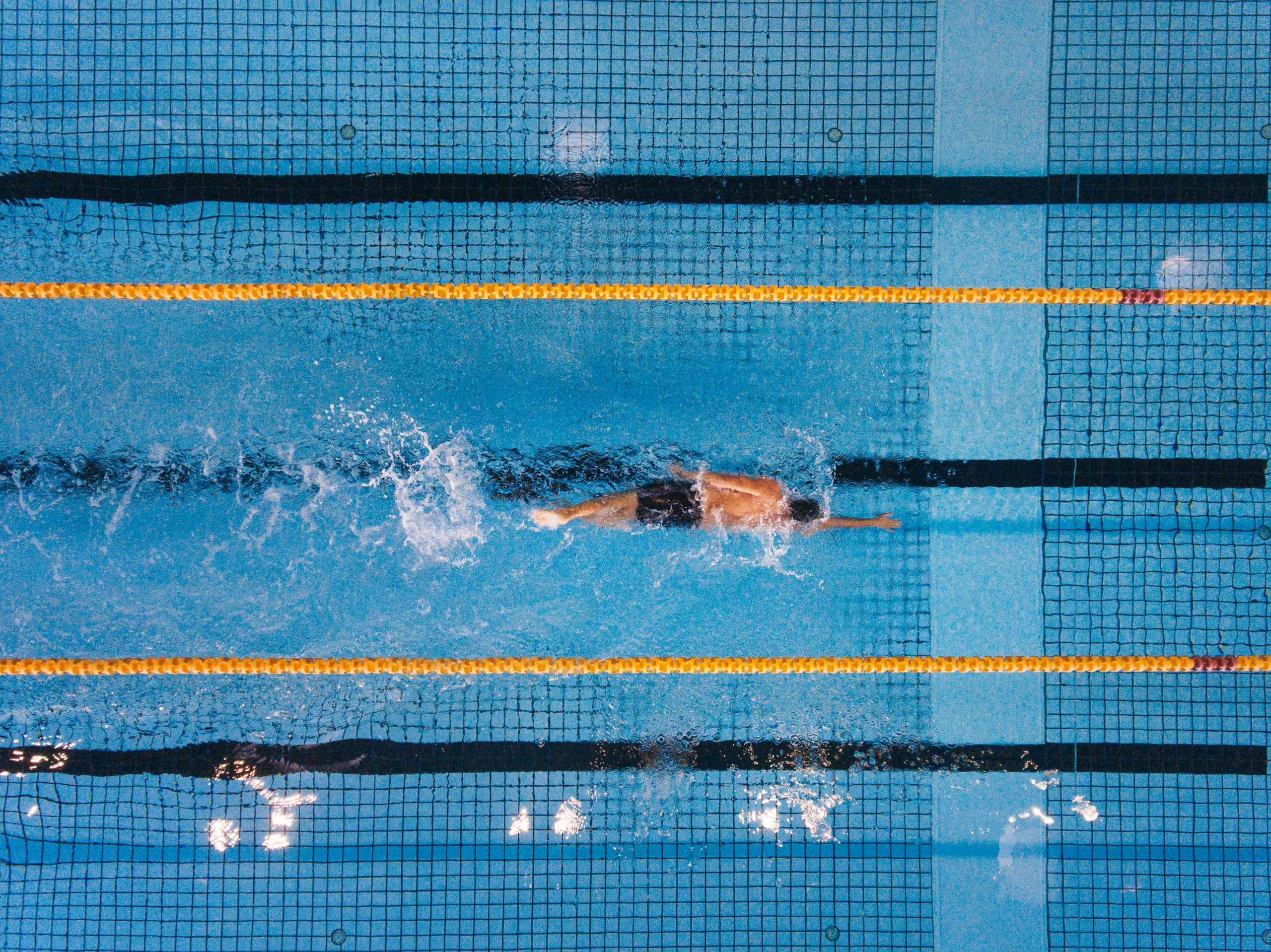 social distancing sports | overhead shot of man swimming laps in pool